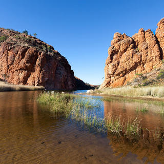 Glen Helen Waterhole in front of rocky cliffs near Alice Springs in West Macdonnel Ranges
