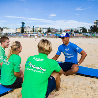 Surf group sitting on the sand with instructor