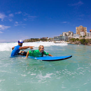 Girl on surfboard with instructor at Bondi Beach